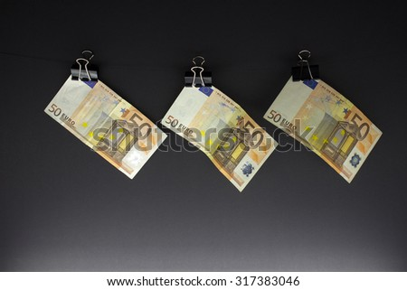Hanging 50 Euro banknots on a string - stock photo