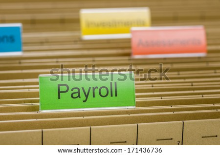 Hanging file folder labeled with Payroll - stock photo