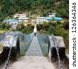 hanging footbridge ower the marsyangdi nadi river- annapurna himal - nepal - stock photo