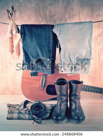 Hanging jeans and corns with shirt and boots over acoustic guitar and grunge background still life style - stock photo