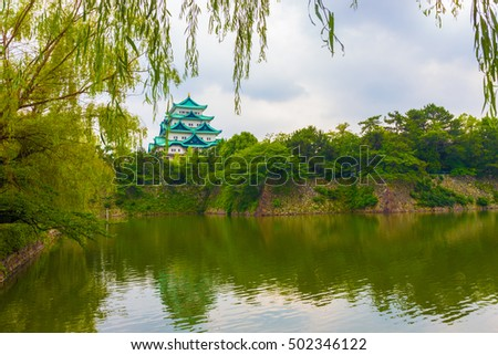Hanging leaves frame the historic Nagoya Castle stronghold beautifully reflected in a watery moat and strong walled rampart in Japan. Horizontal