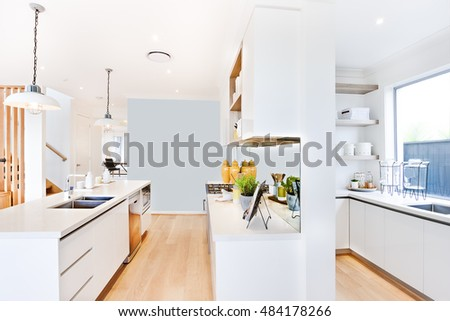 Hanging lights on in the kitchen over the counter top with silver sink and tap, the green color plant in the gray vase beside the mirror under the shelf, the glass window near to the white top