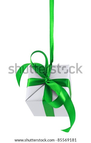 Hanging on a ribbon silver gift wrapped present with green satin bow isolated on white - stock photo