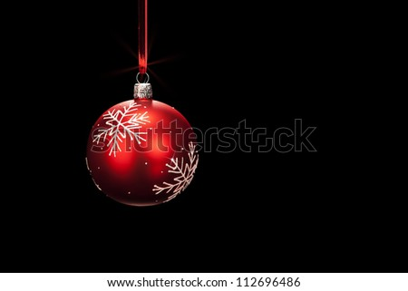 hanging red dull christmas ball on black background - stock photo