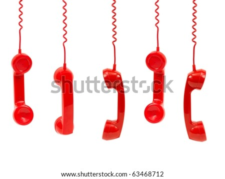 Hanging rotary telephone hand sets isolated against a white background - stock photo
