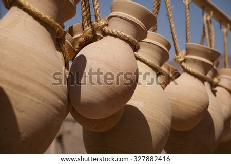 Hanging rough clay jars on the strings - stock photo