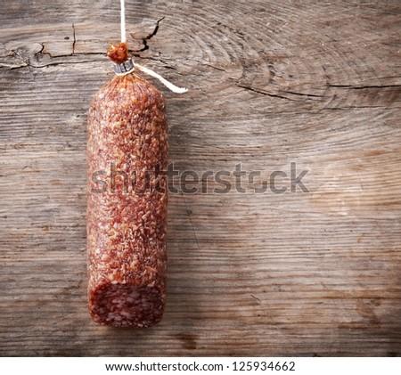 hanging salami sausage on wooden background - stock photo