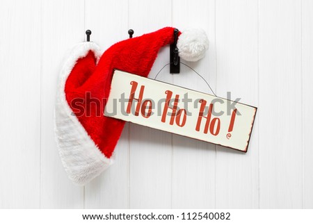 Hanging Santa Claus hat with hohoho sign - landscape version - stock photo