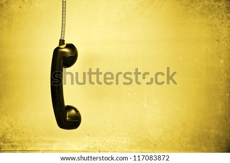 Hanging vintage phone receiver over a grunge background - stock photo