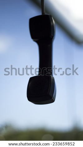Hanging vintage phone receiver over a urban background. - stock photo