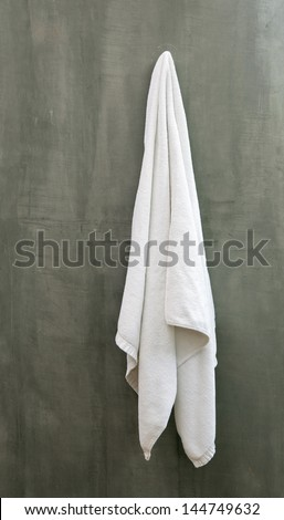 Hanging White Towel draped on Exposed Concrete Wall in the Bathroom - stock photo