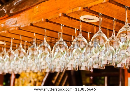 hanging wine glasses in a bar - stock photo