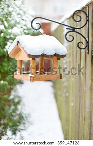 Hanging wooden bird feeder covered by snow in winter. Outdoors vertical closeup image. - stock photo