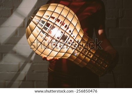 Hanging, wooden light shade lamp with bulb in hands - stock photo