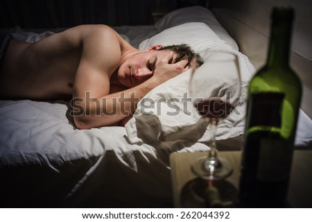 Hangover Man with Headaches in a Bed at Night and Wine bottle - stock photo