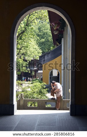 HANGZHOU, CHINA - MAY 4, 2015: Chinese man standing outside a building at the Lingyin Temple, a Buddhist temple of the Chan sect located north-west of Hangzhou, Zhejiang Province, and important landmark.