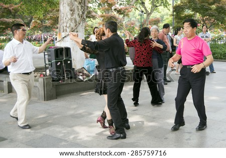 HANGZHOU, CHINA - MAY 3, 2015: Chinese people dancing by the Xihu (West Lake), celebrating their traditions. The West Lake has influenced poets and painters throughout China for its natural beauty. - stock photo