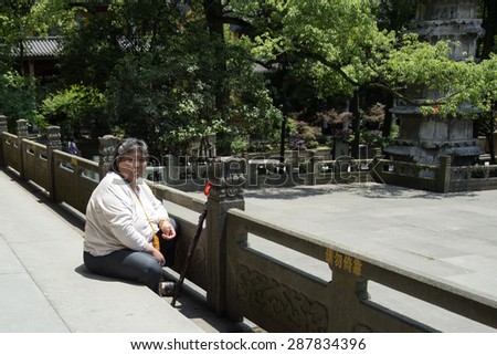 HANGZHOU, CHINA - MAY 4, 2015: Chinese tourist resting at the Lingyin Temple, a Buddhist temple of the Chan sect located north-west of Hangzhou, Zhejiang Province, and important landmark. - stock photo