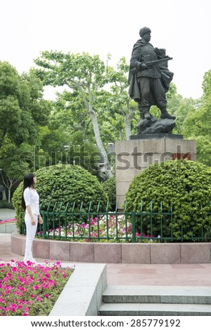 HANGZHOU, CHINA - MAY 3, 2015: Chinese woman admiring a statue of a soldier in honor of the Chinese army men who participated in the Korean War, defending North Korea. - stock photo
