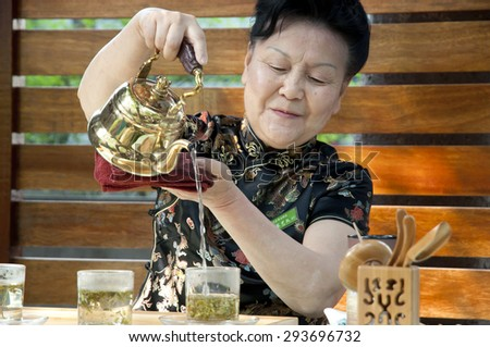 HANGZHOU, CHINA - MAY 5, 2012: Local Chinese woman demonstrates green tea pouring in a small bar