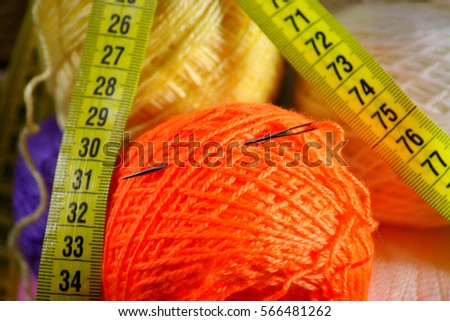 Hank of orange yarn with a darning needle and centimeter band for measurements