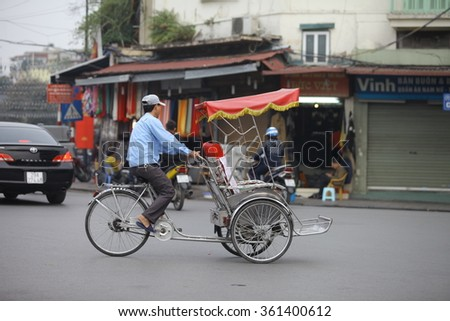 Hanoi, Vietnam: An unidentified tourist sits in traditional cycle vehicle in the busy Hanoi traffic on January 8, 2016. Cyclo is the tourist's farvourite vehicle transportation in vietnam