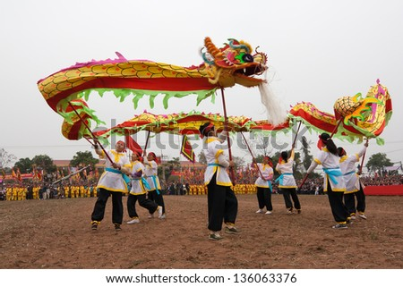HANOI, VIETNAM - APRIL 12: A group of unidentified boys dance with their colorful dragons during the Tet Lunar New Year celebrations on April 12, 2008 in Ha Noi City, Vietnam. - stock photo