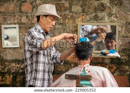 HANOI, VIETNAM - APRIL 8: Unidentified barber cut hair on street on April 8, 2014 in Hanoi, Vietnam. Barber who doesn't have a shop have to work on street. - stock photo