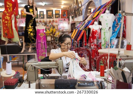 Hanoi, Vietnam - 30 April 2014: Vietnamese tailor woman sews traditional silk dress 'Ao dai' on 30 April 2014, Hanoi, Vietnam.
