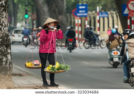 HANOI, VIETNAM, DECEMBER 15, 2014 : A peddler carrying a traditional balance is selling bananas and pineapple in the streets of Hanoi, Vietnam - stock photo