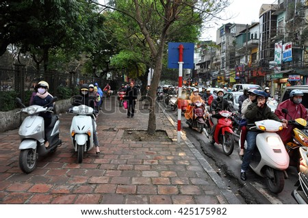 HANOI, VIETNAM - FEBRUARY 19, 2013: Crowd of people with scooters blocked in a traffic jam, waiting for green light on the streets of Hanoi.  - stock photo