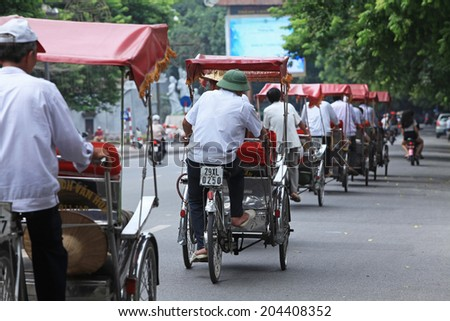 HANOI, VIETNAM - JUL 12, 2014: Life in Vietnam - cyclo line in Sword lake. Cyclo is one of the most favorite vehicles for tourist when come to Vietnam's cities.  - stock photo