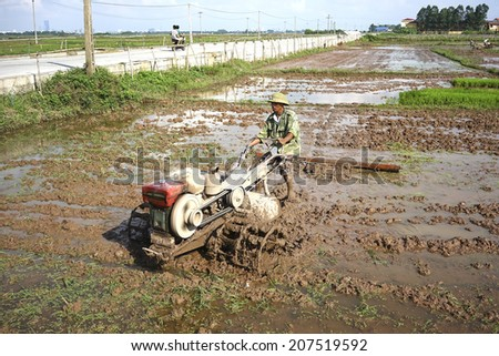 HANOI, VIETNAM - JULY 13, 2014: Unidentified Vietnamese farmer handling a tractor in the paddy field in a rural area of Hanoi at the beginning of a new season.
