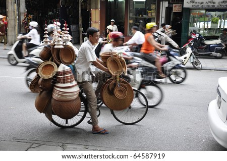 HANOI, VIETNAM - JUNE 29: Unidentified hat salesman in the busy Hanoi traffic on June 29, 2010 in Hanoi, Vietnam