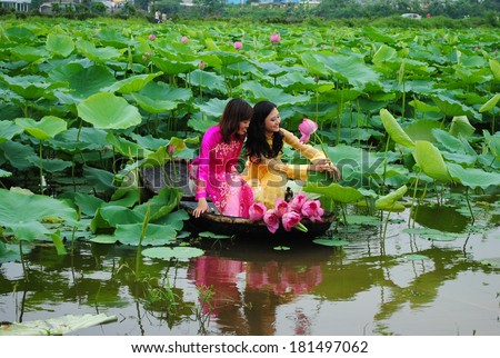 HANOI, VIETNAM, JUNE 12: Unidentified Vietnamese girls wear Ao dai and sit on boat in lake of lotus on June 12, 2010 in Hanoi, Vietnam. Ao dai is famous traditional custume for woman in VIetnam.