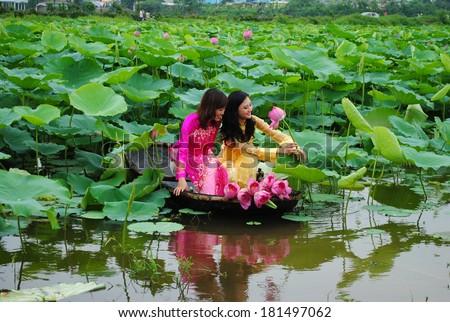 HANOI, VIETNAM, JUNE 12: Unidentified Vietnamese girls wear Ao dai and sit on boat in lake of lotus on June 12, 2010 in Hanoi, Vietnam. Ao dai is famous traditional custume for woman in VIetnam.