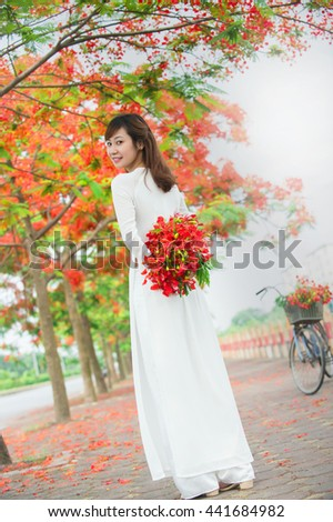 Hanoi, Vietnam, May 21th, 2016: Hanoi girl is charming in long-dress (the Ao dai - Vietnamese) and Royal Poinciana road (Delonix Regia). The Ao dai is traditional costume of Vietnamese woman.