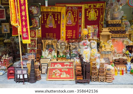 Hanoi, Vietnam - Nov 1, 2015: Worshiping objects for sale on Hanoi street: funeral flag, altar, flower lantern...Offerings in Oriental culture