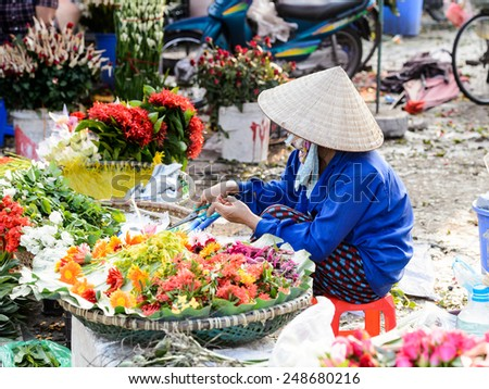 HANOI, VIETNAM - SEP 23, 2014: Unidentified Vietnamese woman works at the flower market. 92% of Vietnamese people belong to the Viet ethnic group - stock photo