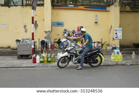 Hanoi, Vietnam - Sep 2, 2015: Vietnamese man on motorcycle buying cocking oil at a flea mobile stall on the side walk of a street in Hanoi capital. - stock photo
