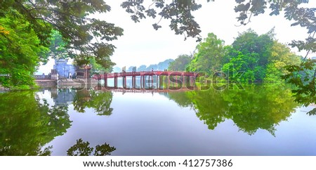 Hanoi, Vietnam - 29th September 2015: Architectural Huc Bridge looming shake trees lake with arched red craw fish culture symbolizes history thousands years in Hanoi, Vietnam - stock photo