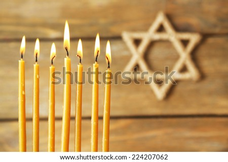 Hanukkah candle on wooden background - stock photo