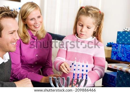 Hanukkah: Little Girl Lights Menorah Candles To Celebrate - stock photo