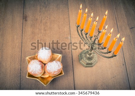 Hanukkah menorah and jelly donuts on wooden table. Retro style filtered photo - stock photo