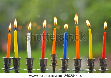 Hanukkah menorah lit with eight candles at the last day of Hanukah. - stock photo