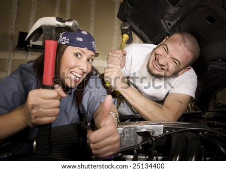 Hapless mechanics working on car engine with hammers - stock photo
