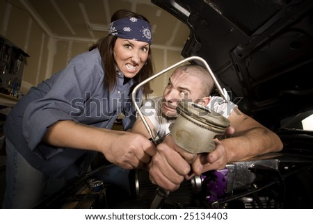 Hapless mechanics working on car engine with the wrong tools - stock photo