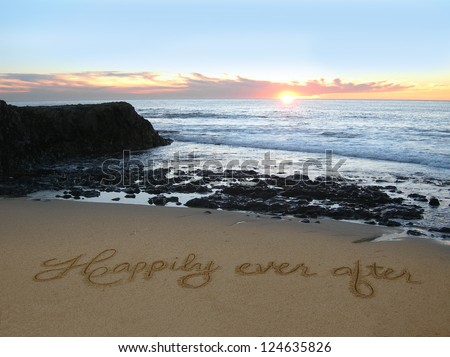 Happily Ever After handwritten in sand with rocks jutting out in background - stock photo