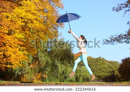 Happiness and freedom. Casual young woman girl jumping with blue umbrella in autumnal park, having fun outdoor - stock photo