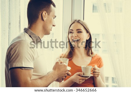 Happiness and healthy relationship concept. Attractive couple drinking tea or coffee together at home, man and woman holding cups with hot beverage at home - stock photo